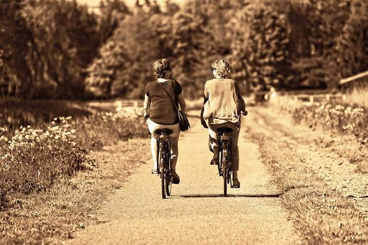 This shows two older ladies riding bikes